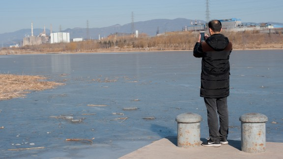 Environmental activist Ma Jun uses his smartphone to upload photos of a disused steel plant to his anti-pollution app on January 18.
