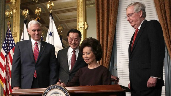 Elaine Chao, Trump's pick for transportation secretary, signs the affidavit of appointment during her swearing-in ceremony in Washington on Tuesday, January 31. Chao is joined, from left, by Pence; her father, James Chao; and her husband, Senate Majority Leader Mitch McConnell.