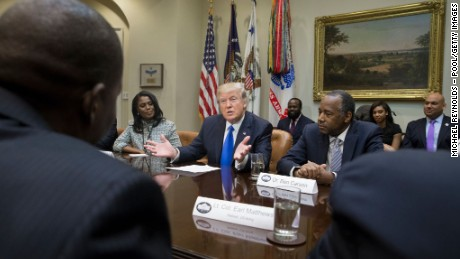President Donald Trump holds an African American History Month listening session attended by nominee to lead the Department of Housing and Urban Development (HUD) Ben Carson (R), Director of Communications for the Office of Public Liaison Omarosa Manigault (L) and other officials in the Roosevelt Room of the White House on February 1, 2017 in Washington, DC.