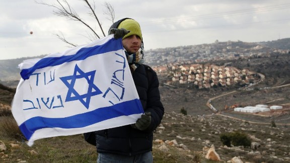 An Israeli settler holds a flag with slogans at the Amona outpost, northeast of Ramallah, on February 1, 2017.