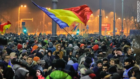 Many protesters wave Romanian flags or hold up signs Wednesday in Bucharest.