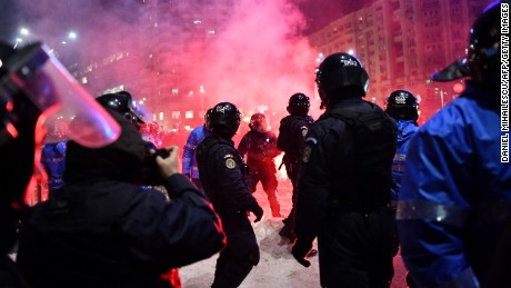 Riot police clash with protesters Wednesday in front of government headquarters in Bucharest.