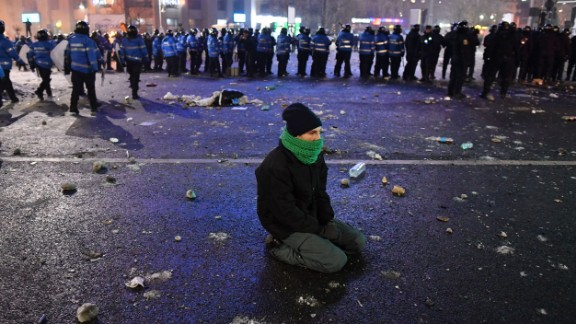 A protester kneels near a police line on February 1 in Bucharest.