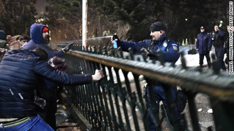 An officer uses pepper spray on protesters trying to enter government headquarters Tuesday.