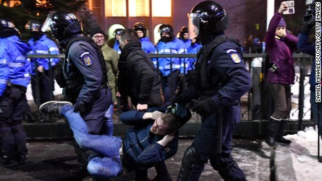 Romanian anti-riot police evacuate a protester during the anti-amnesty demonstrations in Bucharest.