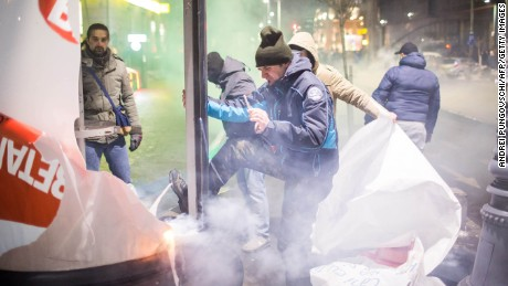 Demonstrators dismantle advertisements during protests Wednesday in Bucharest.