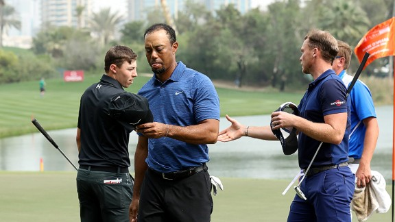 A dejected-looking Woods leaves the ninth green at the end of his first round as playing partners Matthew Fitzpatrick and Masters champion Danny Willett of England shake hands behind him.