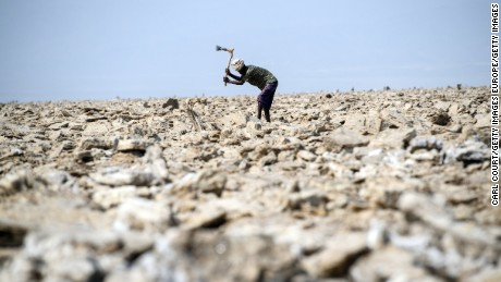 DALLOL, ETHIOPIA - JANUARY 23:  A salt miner works in the heat as he digs out salt blocks by hand in the Danakil Depression on January 22, 2017 in Dallol, Ethiopia. The depression lies 100 metres below sea level and is one of the hottest and most inhospitable places on Earth. Despite the gruelling conditions, Ethiopians continue a centuries old industry of mining salt from the ground by hand in temperatures that average 34.5 degrees centigrade but have risen to over 50 degrees.  (Photo by Carl Court/Getty Images)