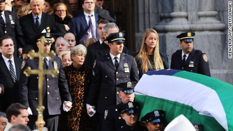 Patti Ann McDonald and son Conor follow Steven McDonald's casket at his funeral last month.