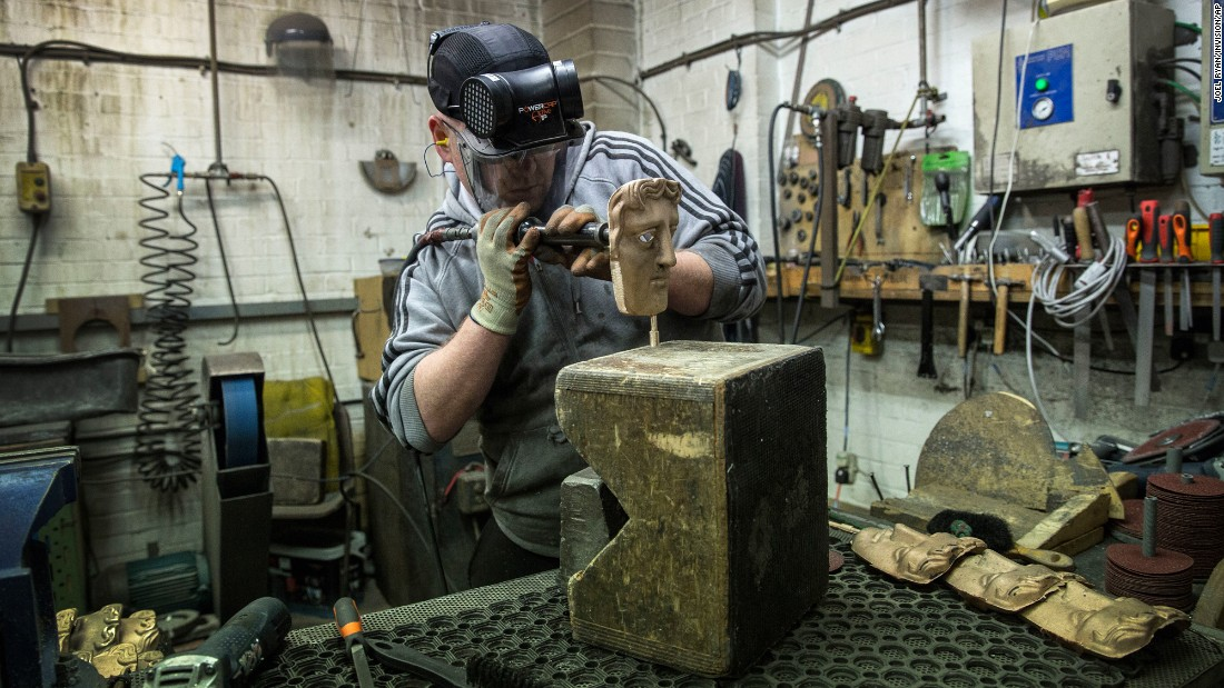 A fettler works on a bronze alloy British Academy of Film and Television Arts (BAFTA) mask at a foundry in West Drayton, England, on Tuesday, January 31, ahead of the award ceremony set to take place later this month. The iconic BAFTA mask was designed in 1955 by US sculptor Mitzi Cunliffe.