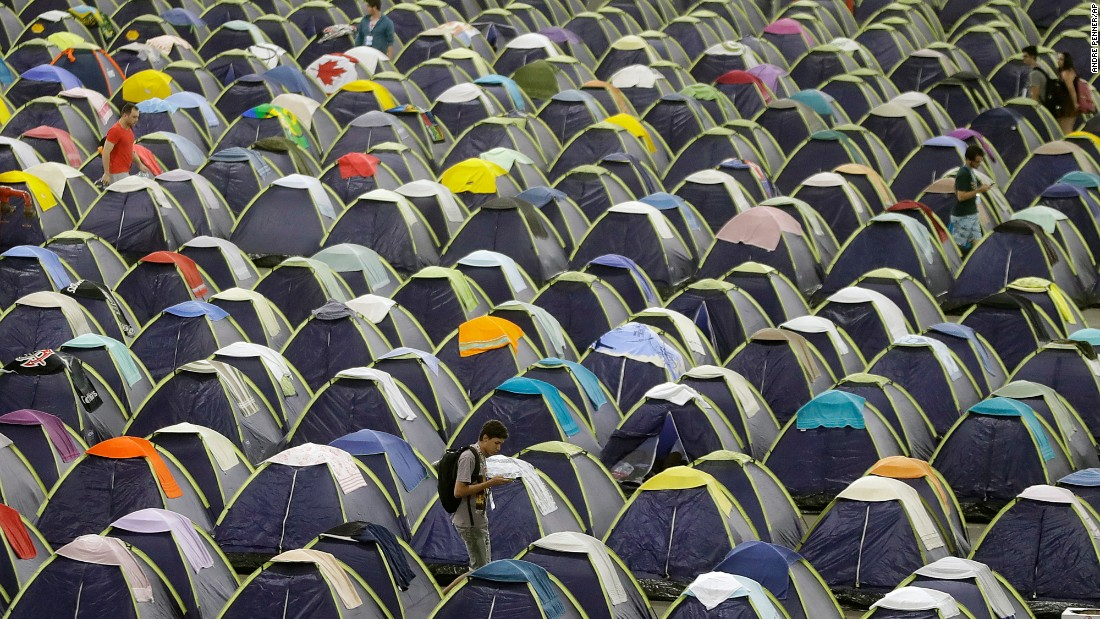 A participant walks between rows of tents in the camping area of Campus Party in Sao Paulo, Brazil, on Wednesday, February 1. According to its website, Campus Party is an annual weeklong, 24-hour-a-day technological experience that brings together developers, gamers and hackers for a festival geared toward innovation, creativity, science and entrepreneurship entertainment.