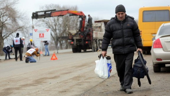 """A local resident walks past Red Cross employees installing billboards reading """"Danger! Mines! Do not leave the road!"""" near Berezove in Donetsk region in March 2016."""