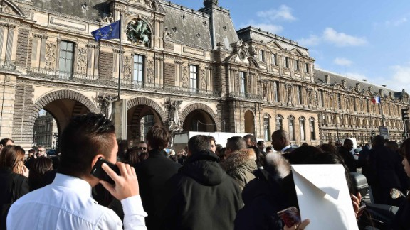 People stand in front of the Louvre museum on February 3, 2017 in Paris after a soldier has shot and gravely injured a man who tried to attack him.