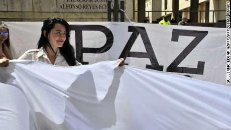 A woman holds a white flag during a demonstration to demand the immediate endorsement of the new peace agreement between the Colombian government and the FARC guerrilla outside the Colombia's Constitutional Court in Bogota, on December 12, 2016. Colombian Constitutional Court has to debate the approval of a fast track mechanism that would speed up voting on bills linked to the peace process, including amnesty for FARC guerrillas. The Colombia's Congress approved the government's controversial revised peace deal to end a half-century conflict with leftist FARC rebels after voters on October 2 surprisingly snubbed an earlier version of the accord in a referendum. / AFP / Guillermo LEGARIA        (Photo credit should read GUILLERMO LEGARIA/AFP/Getty Images)