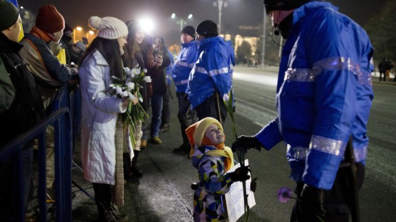 A young girl offers a flower to a police officer during an anti-government protest February 2 in Bucharest.