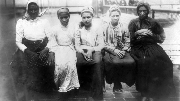 Five newly arrived immigrants sit on a dock at Ellis Island in 1910.