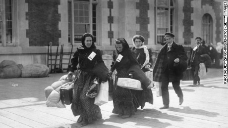 A group of immigrants carry their belongings after arriving at Ellis Island, New York, in the early 1900s.