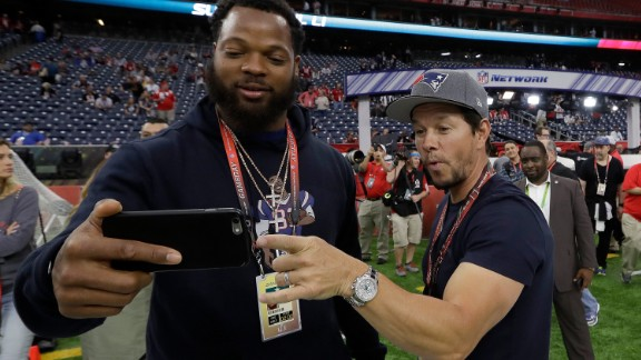 Seattle defensive end Michael Bennett takes a selfie with actor Mark Wahlberg before the game. Bennett