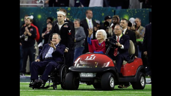 Former President George H.W. Bush and his wife, Barbara, wave as they arrive for the pregame coin toss. They were both recently hospitalized.