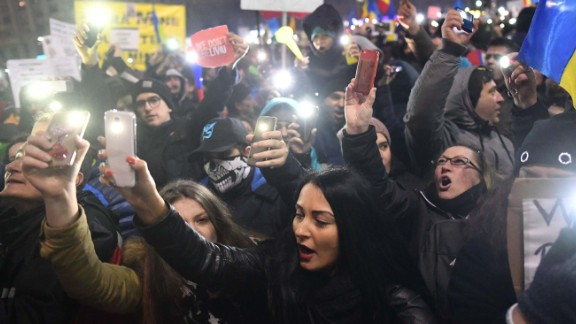 Protesters shine their mobile phone lights as they protest in front of government buildings Sunday
