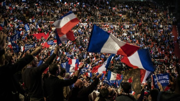 Supporters wave flags as they attend a rally of the French far-right National Front (FN) party presidential candidate to kick off her campaign in Lyon on February 5, 2017.  / AFP / JEFF PACHOUD        (Photo credit should read JEFF PACHOUD/AFP/Getty Images)