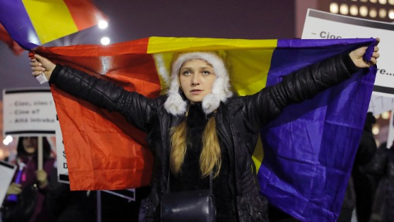 A woman displays a Romanian flag during a protest in Bucharest on Friday, February 3.