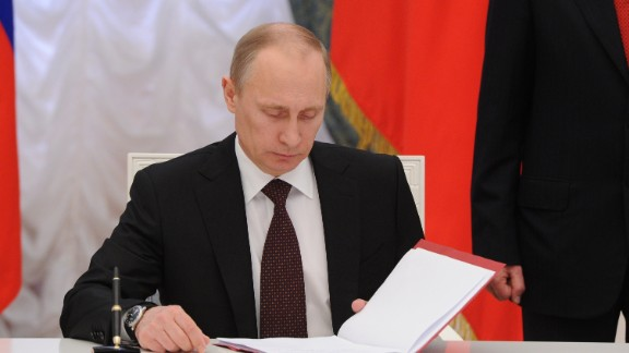 Russia's President Vladimir Putin prepares to sign a law on ratification of a treaty making Crimea part of Russia, during a ceremony in the Kremlin in Moscow March 21, 2014. Putin said today Moscow would hold off on further reciprocal sanctions against the United States, after Washington introduced punitive measures against his close allies over the Ukraine crisis. AFP PHOTO/ RIA-NOVOSTI/ POOL / MIKHAIL KLIMENTYEV        (Photo credit should read MIKHAIL KLIMENTYEV/AFP/Getty Images)