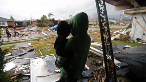 Eshon Trosclair holds her son Camron Chapital after a tornado tore through home while they were inside.