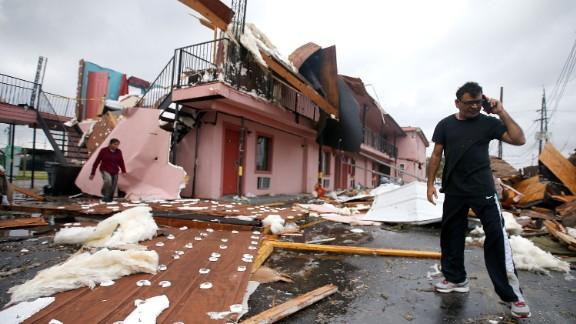 A man talks on the phone amid the debris of a motel.