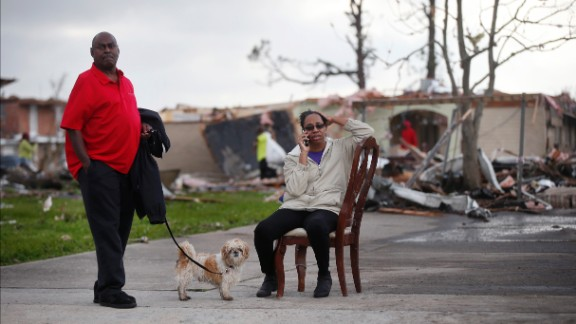 Across the street from her  destroyed home, Claire White sits in a chair and talks on the phone next to her husband, Roy, and dog JD.