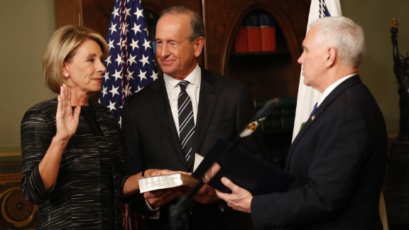 Pence swears in Education Secretary Betsy DeVos next to her husband, Dick, on Tuesday, February 7. Pence cast a historic tie-breaking vote to confirm DeVos after the Senate was divided 50-50.