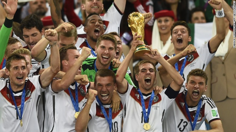 Germany's defender and captain Philipp Lahm (front-R) holds up the World Cup trophy as he celebrates on with his teammates after winning the 2014 FIFA World Cup final football match between Germany and Argentina 1-0 following extra-time at the Maracana Stadium in Rio de Janeiro, Brazil, on July 13, 2014.  AFP PHOTO / FABRICE COFFRINI        (Photo credit should read FABRICE COFFRINI/AFP/Getty Images)