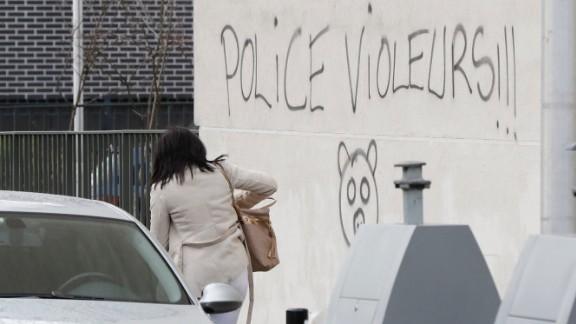 "A woman walks next to graffiti reading ""police rapists."""