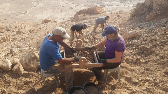 The team sifts through material near the newly discovered cave.