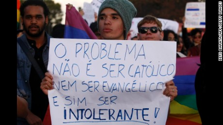 "A protester against homophobia at a march in Brasilia, Brazil holds a sign that reads: ""The problem is not being Catholic or being Evangelical, but being intolerant."""