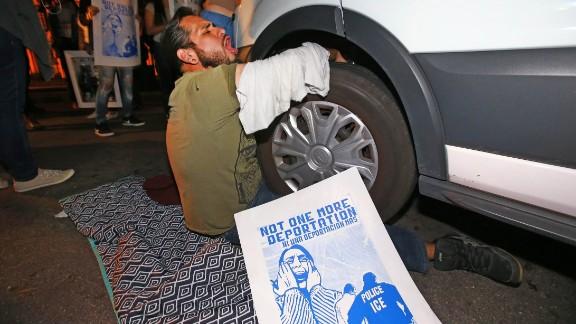 A protester locks himself to the van carrying Garcia de Rayos away.
