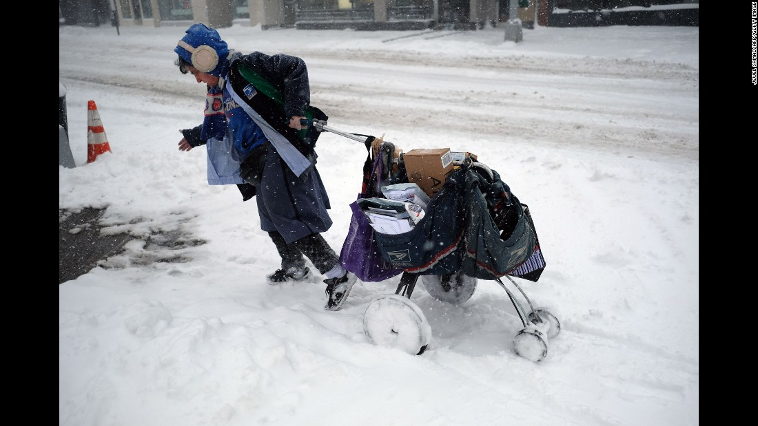 A postal worker drags her mail cart on a snow-covered street in New York on February 9.