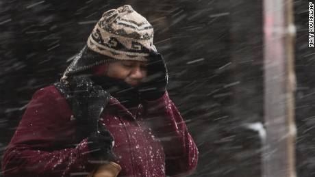 A woman shields her face during a winter storm in Philadelphia, Thursday, February 9, 2017. A powerful, fast-moving storm swept through the northeastern U.S. Thursday, making for a slippery morning commute and leaving some residents bracing for blizzard conditions.