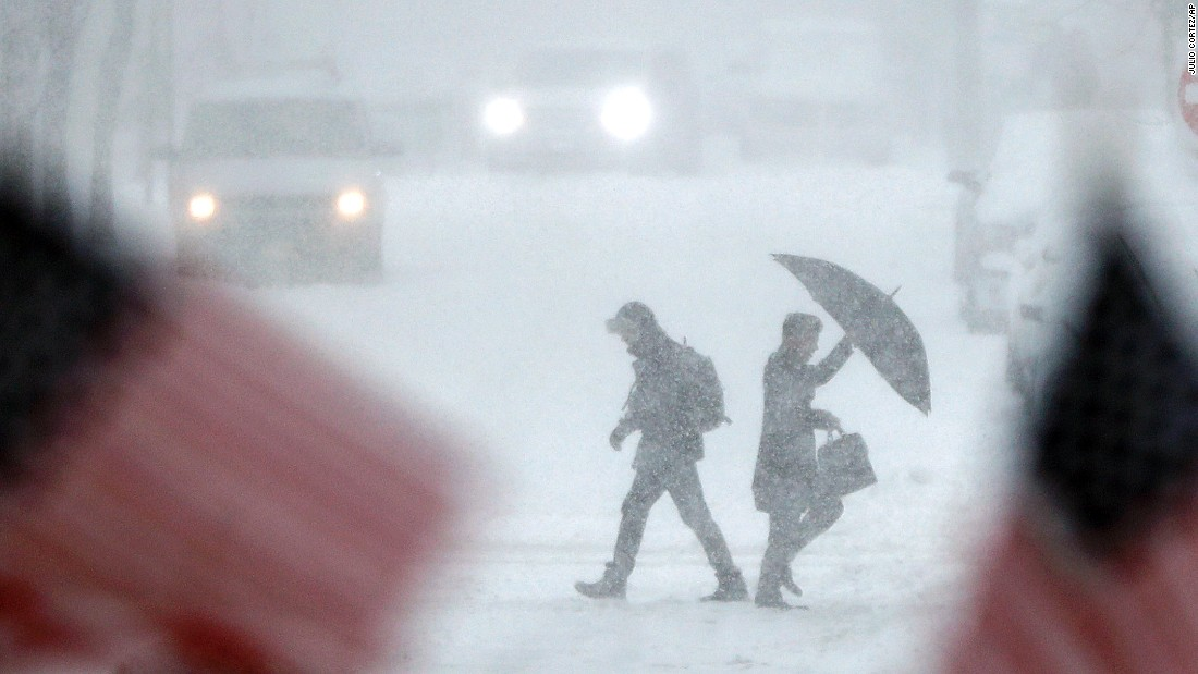 People walk across a snow-covered intersection in Hoboken, New Jersey, on February 9.