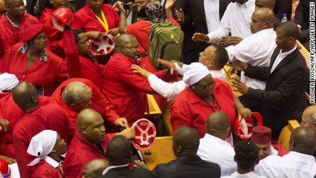 Members of the Economic Freedom Fighters, wearing red uniforms, clash with security forces during the South African President's State of the Nation address in Cape Town on February 12, 2015.