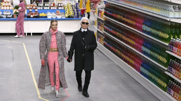 German fashion designer Karl Lagerfeld, flanked by British model Cara Delevingne, acknowledges the audience at the end of Chanel 2014/2015 Autumn/Winter ready-to-wear collection fashion show, on March 4, 2014 at the Grand Palais in Paris.  AFP PHOTO / PATRICK KOVARIK        (Photo credit should read PATRICK KOVARIK/AFP/Getty Images)