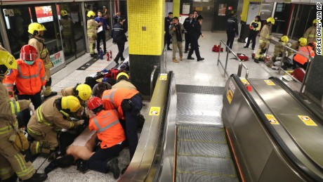 Passengers receive medical treatment from firefighters in Tsim Sha Tsui subway station in Hong Kong, Friday, Feb. 10, 2017. Hong Kong authorities say they have arrested a man for arson after a fire broke out in a subway car injuring thirteen people. (Apple Daily via AP) HONG KONG OUT, TAIWAN OUT, ONLINE OUT, NO ARCHIVE, NO SALES