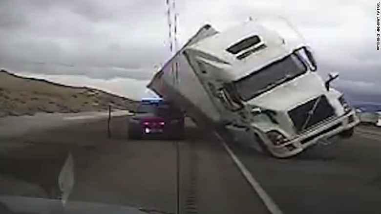 High winds tip a semitrailer onto a patrol car. No one was hurt.