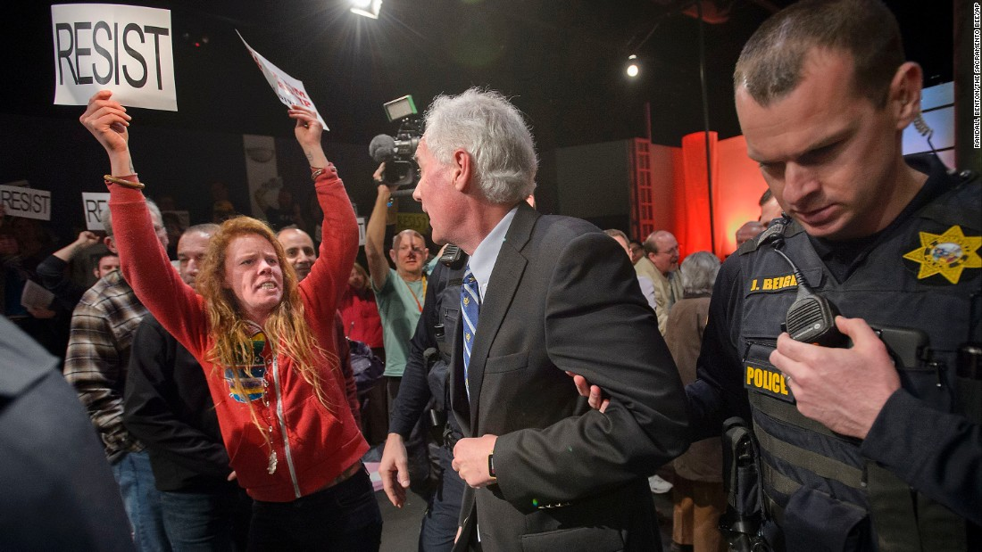 "Police in Roseville, California, escort Republican congressman Tom McClintock past protesters during a town hall meeting at the city's Tower Theatre on Saturday, February 4. Some protesters, upset with McClintock's support for President Trump's agenda, followed him, shouting, ""Shame on you!"""