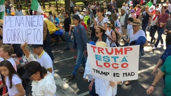 """Protesters hold signs that read """"Peña Nieto is corrupt"""" and """"Trump is crazy."""""""