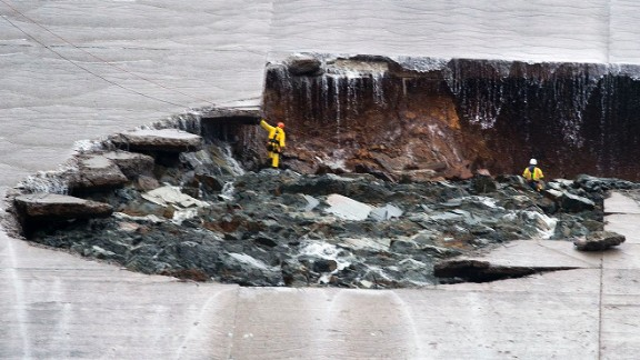 Workers inspect a hole that developed in the main spillway on Wednesday, February 8.