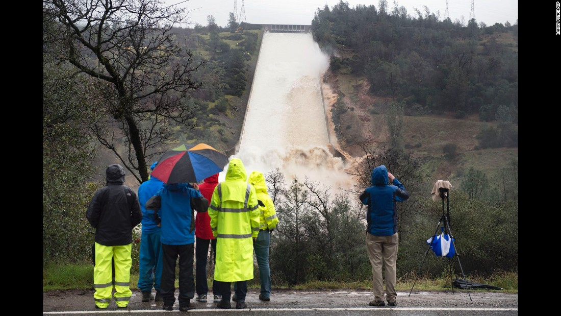 Workers from the Department of Water Resources and members of the media watch as water flows over the main spillway of the Oroville Dam on Wednesday, February 8.