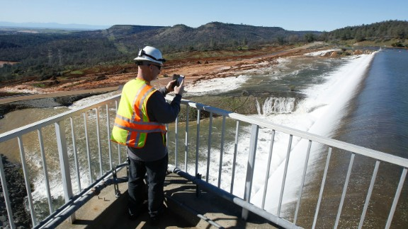 Jason Newton of the California Department of Water Resources photographs water flowing over the emergency spillway alongside the dam on Saturday, February 11.