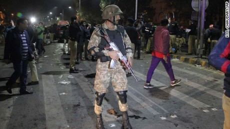 Police and security officers cordon off the area of a deadly bombing, in Lahore, Pakistan, on Monday.