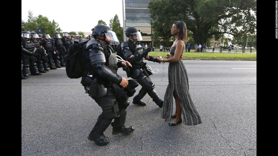 "Ieshia Evans stands in the street July 9 as two police officers move in to arrest her near the headquarters of the Baton Rouge Police Department in Louisiana. Evans was one of hundreds of protesters <a href=""http://www.cnn.com/2016/07/09/us/black-lives-matter-protests/"" target=""_blank"">who blocked a Baton Rouge roadway</a> to decry police brutality."